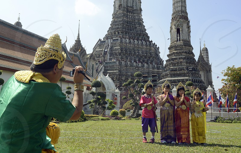 childern in traditional thai clothes in front of the Wat Arun at the Mae Nam Chao Phraya River in the city of Bangkok in Thailand in Southeastasia. photo