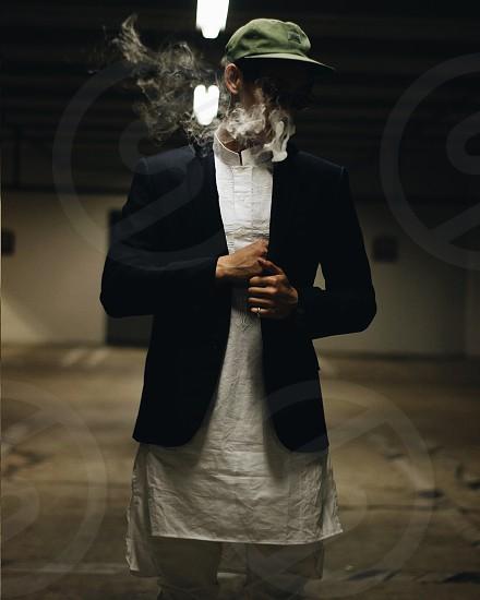 man in black blazer standing and smoking photo