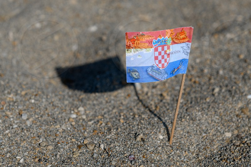 Touristic flag of Croatia picked in Sand on Beach various travel destinations and map of Croatia printed on flag cocktail flag photo
