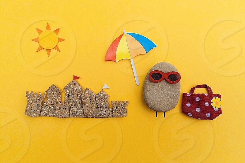 oval brown rock with sunglasses near brown handbag and parasol artwork photo