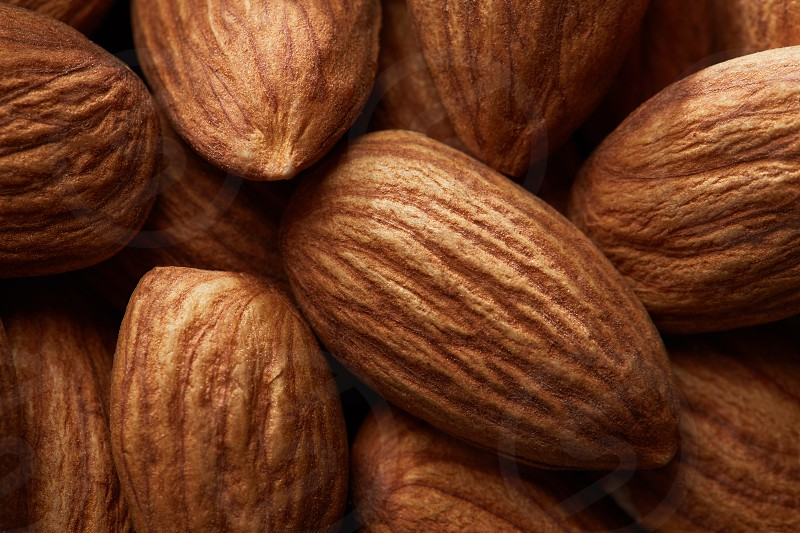 Pile of almonds close-up as background. Almonds background. photo