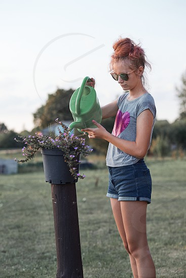 Teenage girl helping to water the flowers growing in flower pot pouring water from green watering can working in backyard at sunset. Candid people real moments authentic situations photo