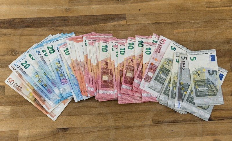 wooden table with euro banknotes in five ten twenty and fifty euro photo