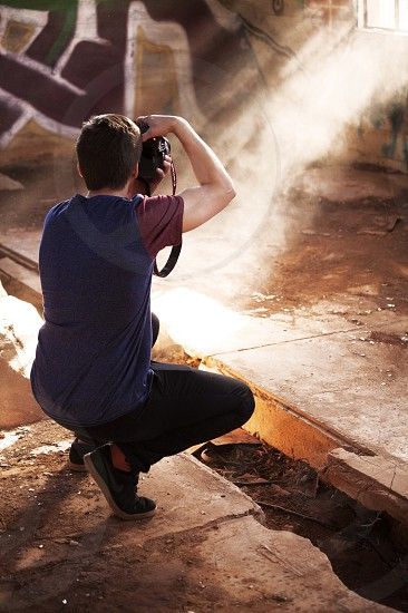 man taking a picture of a light photo