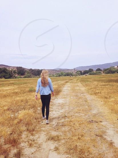 woman walking on dirt path photo