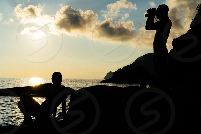 person  on top of rock formation sea side photo