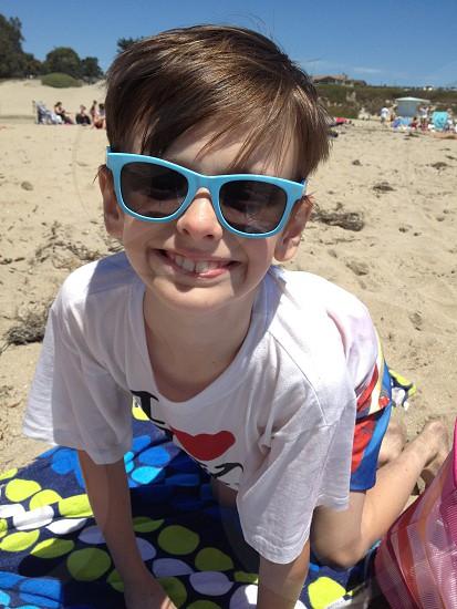 boy in white t shirt wearing blue wayfarer sunglasses smiling photo