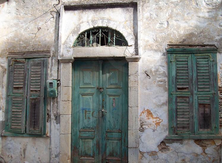 Green door - Greek door - Greek shutter and doors - shutters - peeling paint - architecture - character - stone work - rotting wood - ruin - shabby - eroding - falling down - electricity meter photo