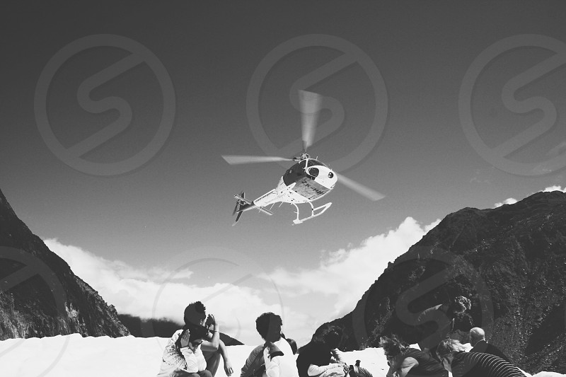 people watching helicopter fly grayscale photography photo