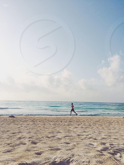 Man running on a tropical beach at sunrise in Tulum Quintana Roo Mexico.  photo