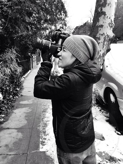 black and white pic of woman in hat and coat taking photo photo