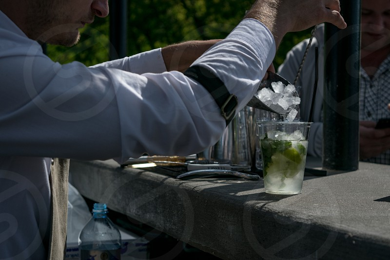 Male bartender puts ice cubes into fresh lemonade in transparent plastic glass photo