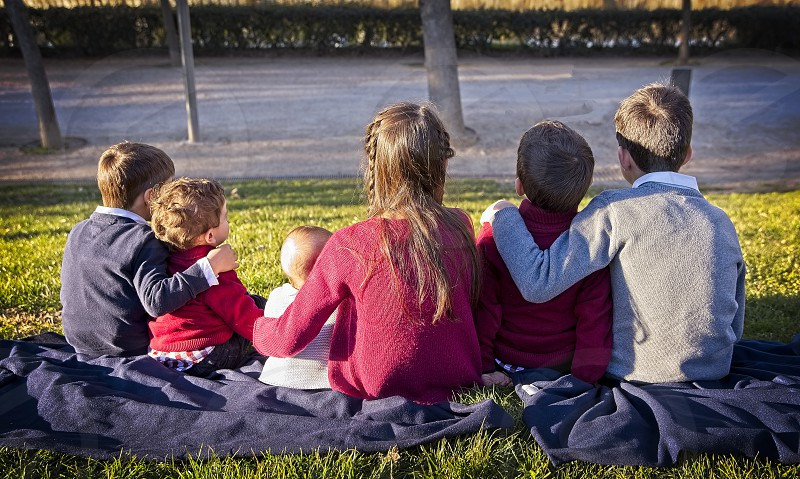 A group of children embraced sitting in the park photo