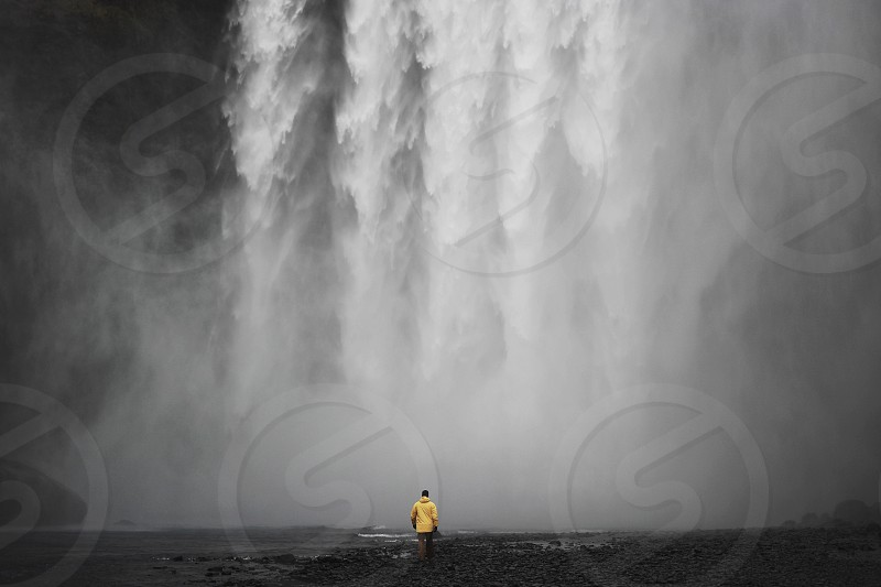 time lapse photo of person wearing yellow jacket near waterfall photo