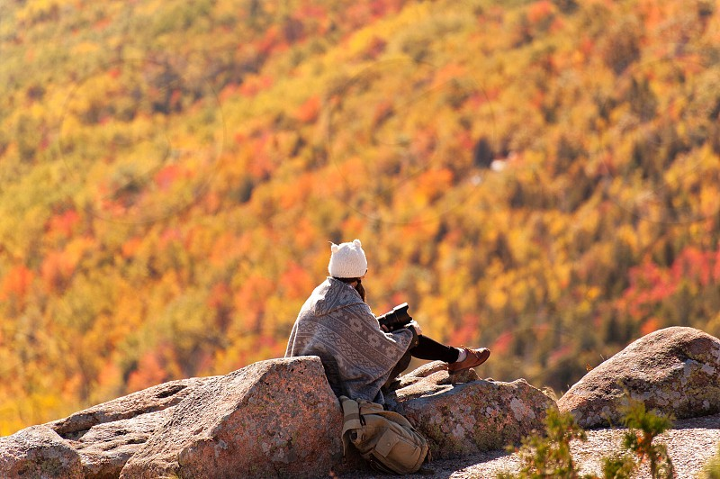 person sitting on rock cliff facing brown leaf trees on mountain during daytime photo