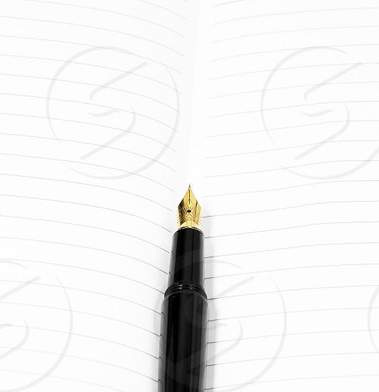 classic black fountain pen on open notebook photo