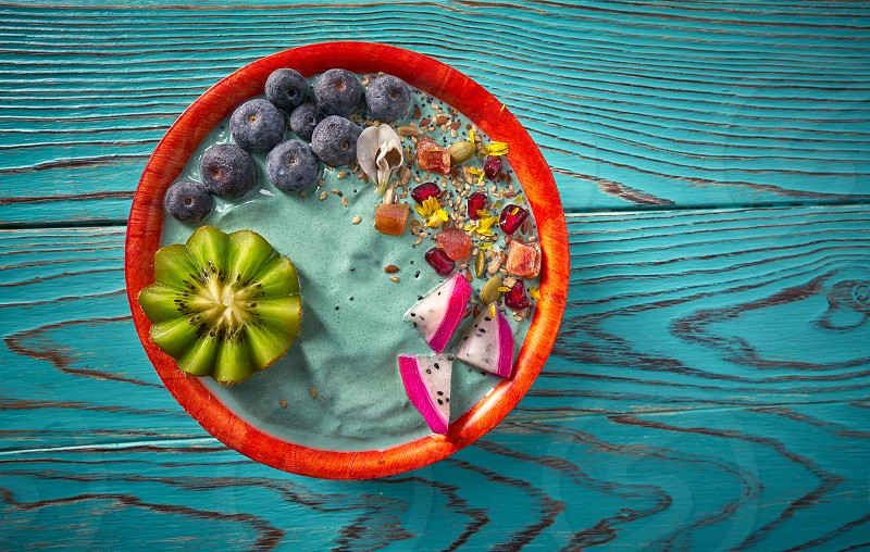 Acai bowl smoothie with kiwi blueberry seeds and pitaya dragon fruit photo