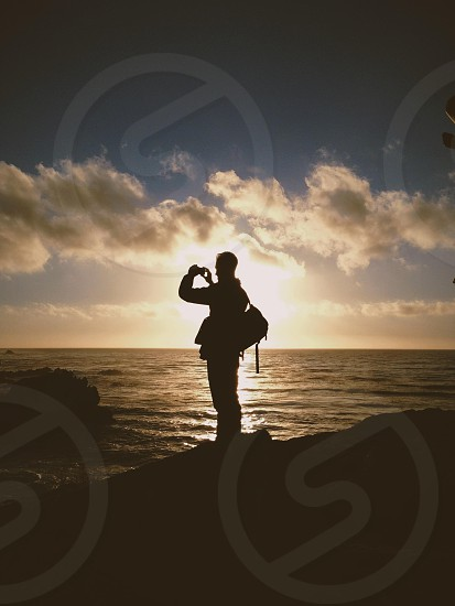 man standing front of sea silhouette photo