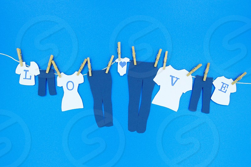 "Modern Romance - Mini cut-outs of family jeans white t-shirts with dark blue letters to spell ""L-O-V-E"" & a baby onesie with a dark blue heart hanging by mini wooden clothespins against a sky blue background photo"