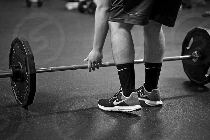 greyscale photography of man about to lift barbell inside gym photo