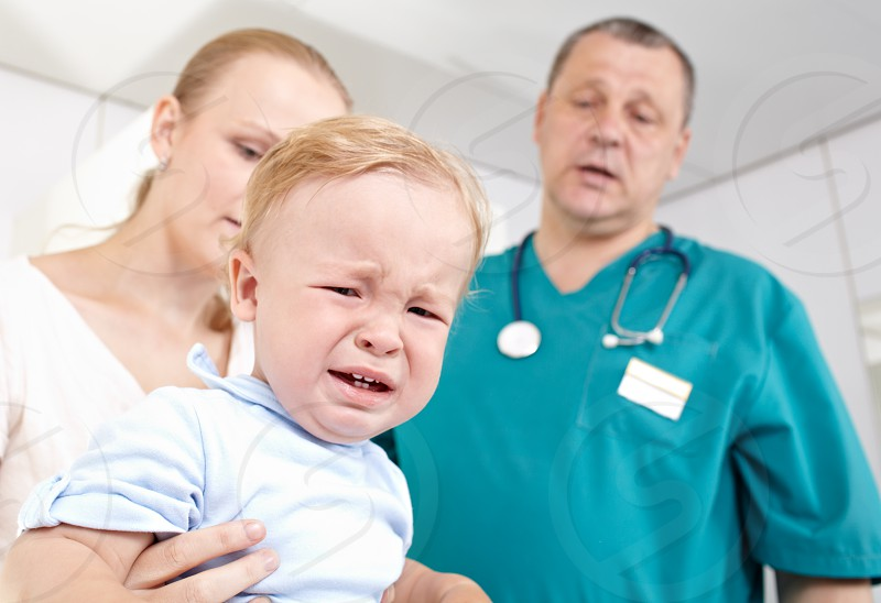 A 15 year-old boy is frightened and crying in a medical study. The doctor and the baby mother are at a loss. Shallow dof. Focus is on the boy. photo