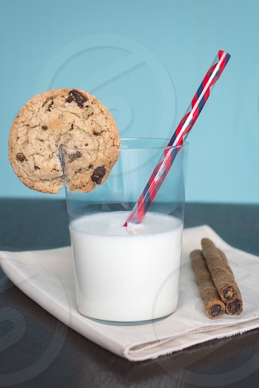 milk in clear drinking glass on table napkin with chocolate wafer stick photo