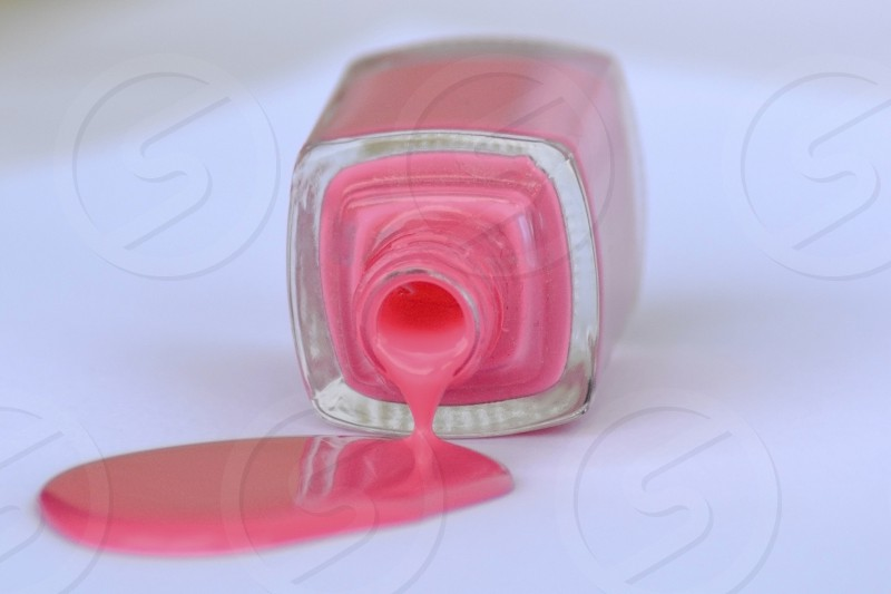 Pink nail polish spilling from bottle on white background. photo