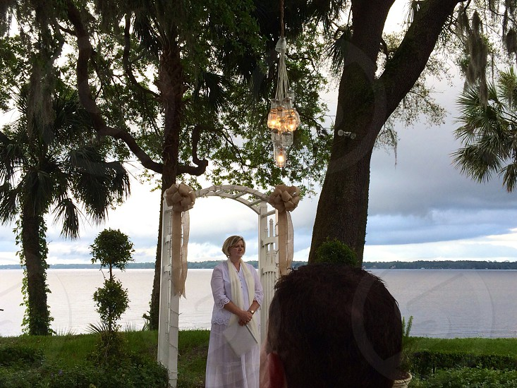 woman in white wedding officiant under trellis near water under cypress tree photo