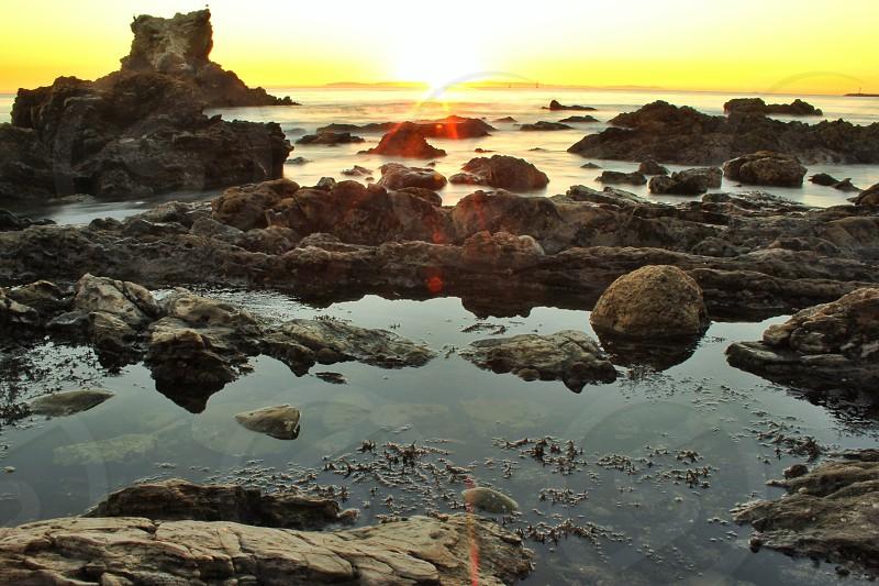 Sunset behind grey ocean rocks photo