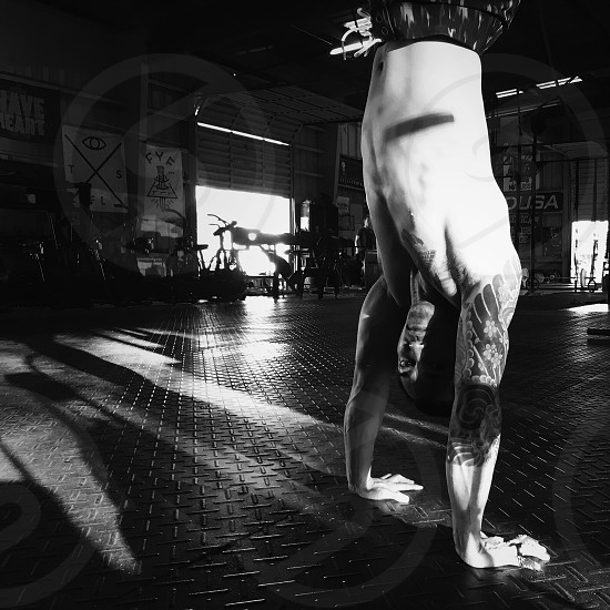grayscale photography of man standing upside down photo