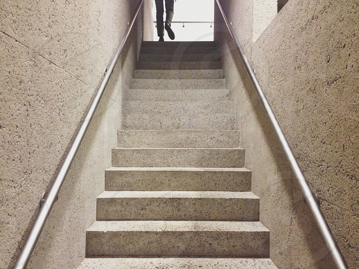 person standing at top of gray concrete staircase photo