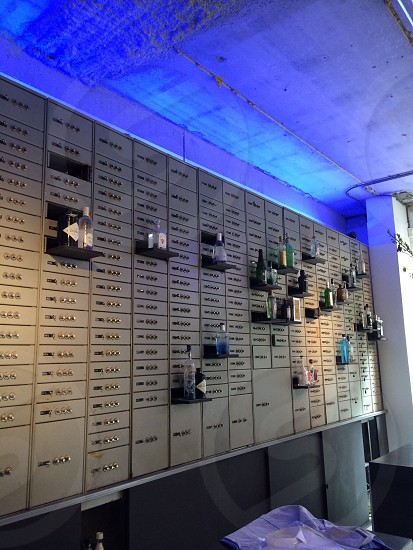 Russian vault wall in a men clothingstore called AERT in Rotterdam with lots of kinds of gin on the shelves photo