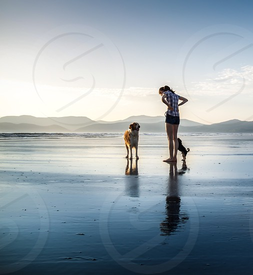 woman and dog standing on seashore photo