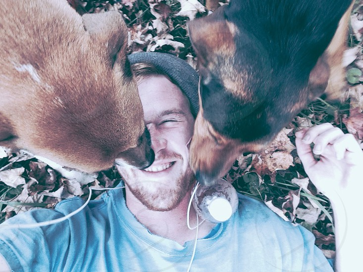 man being licked by two dogs photo