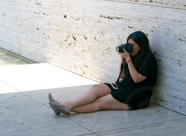woman sitting on the ground taking a photo photo