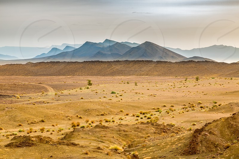 Landscape of southern Morocco is characterized by mountains plains stony soil sand and meager vegetation. photo