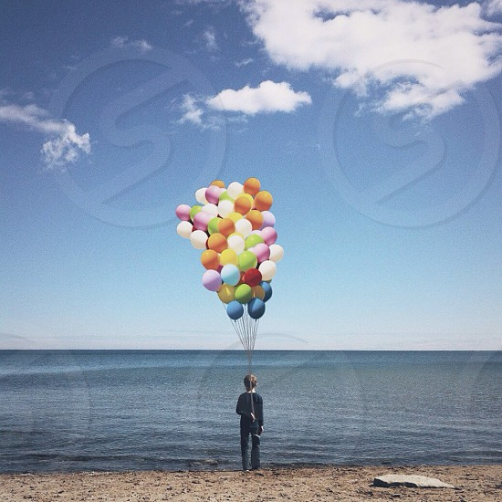 person in black long sleeved shirt holding multicolored balloons photo