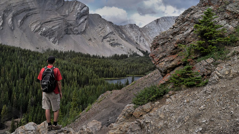 A hiker stands to admire the view of the mountains and nearby lake  photo