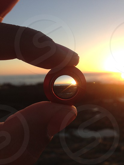 red plastic round toy and a sunset view  photo