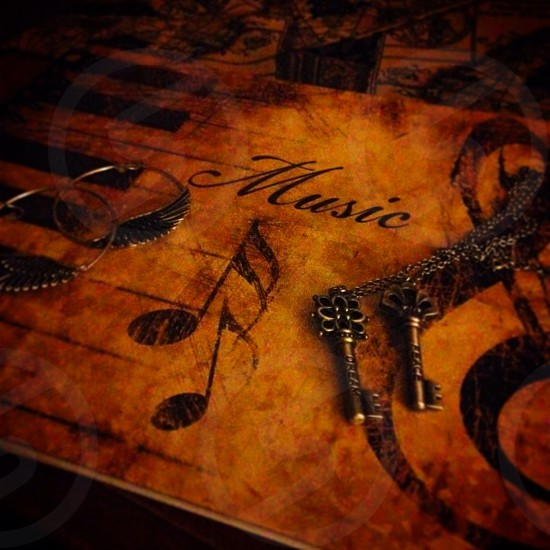 two silver-colored skeleton key pendant necklaces on brown wooden Music-painted board photo