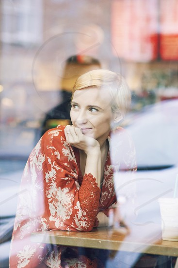woman in orange and white floral long sleeve shirt sitting by the table photo