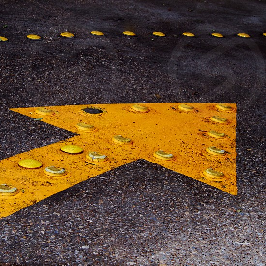 A yellow traffic arrow in a downtown Dallas parking structure. photo