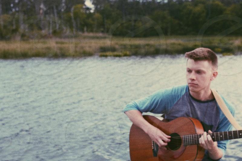 man wearing gray raglan shirt playing guitar photo