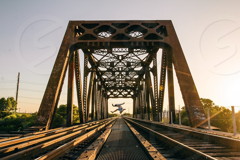 man leaps over railroad at the bridge during sunset photo