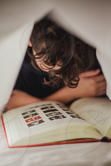 Child reading a book under his sheets  photo