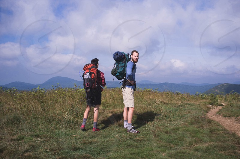 man in blue shirt and khaki shorts standing outside with man in red plaid shirt and black shorts with backpacks on hilltop under cloudy sky photo