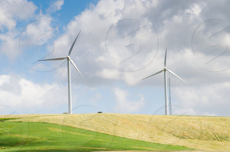 two white wind turbines on a yellow and green hill under a cloudy sky photo