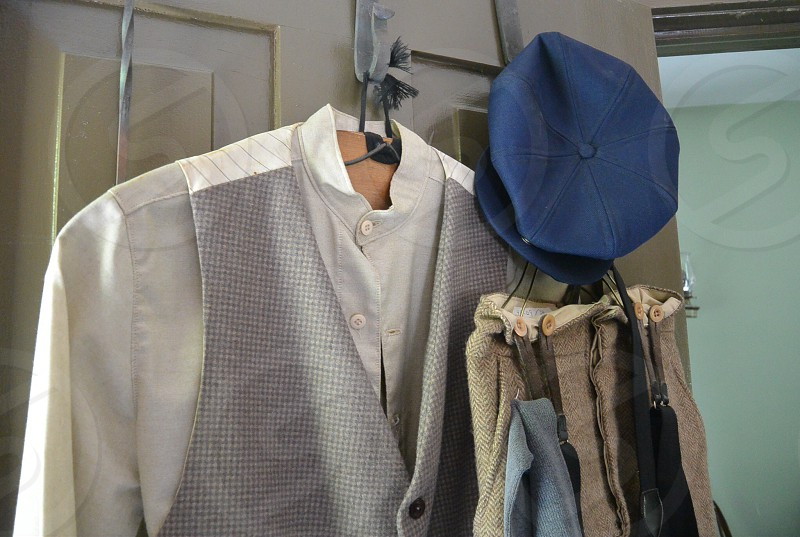 gray and white suit hanging on the white wooden table photo