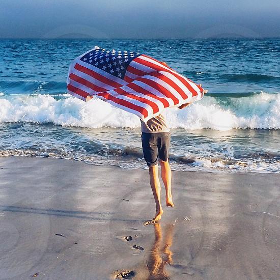 woman holding usa flag on the seashore photo