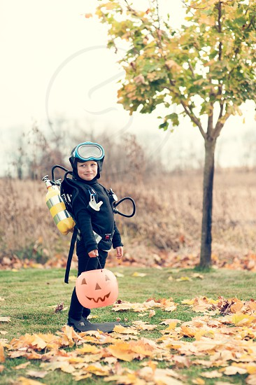 halloween costume boy youth child basket candy scuba diver goggles wetsuit mask kid trick treat autumn leaves october fall black tanks leaves pumpkin grass tree flippers happy smiling photo